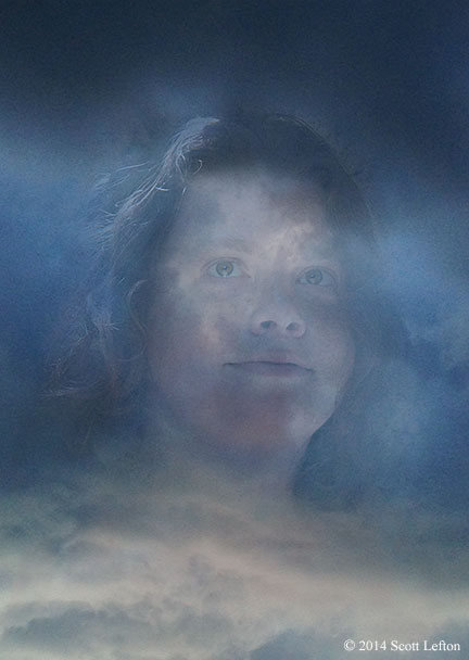 A woman's face is seen in a mass of storm clouds.