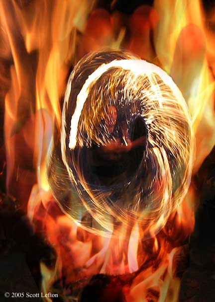 Fire - A hand engulfed in flames holds a man partially hidden behind a spiral of whirling sparks.