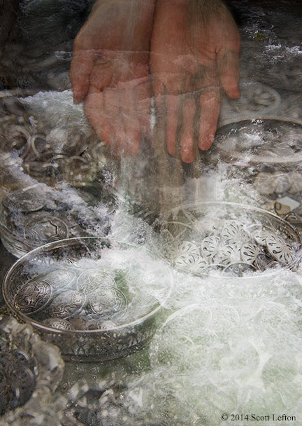 Water cascades over bowls of ornale metal objects, as a pair of semi-transparent hands pour water and sand into the flood.