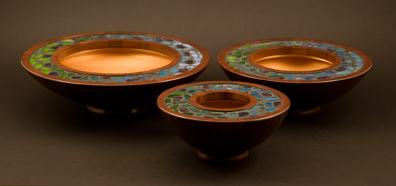 Side view of three mosaic bowls in dark reddish mahogany with green, blue and purple stained glass mosaic inlay, looking somewhat Tiffany.  The inside surfaces are finished in gold acrylic paiint.