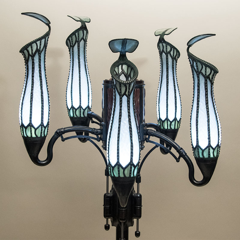 Pitcher Plant Lamp with five heads, all lit by white light to display the stained glass shades.