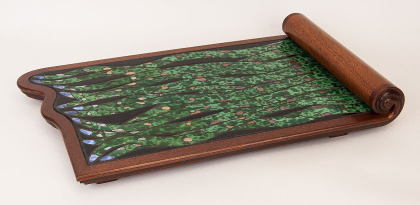The Scroll Tray, with a mahogany frame and mostly green stained glass mosaic making a design of tentacles coming out from under the curved scroll.