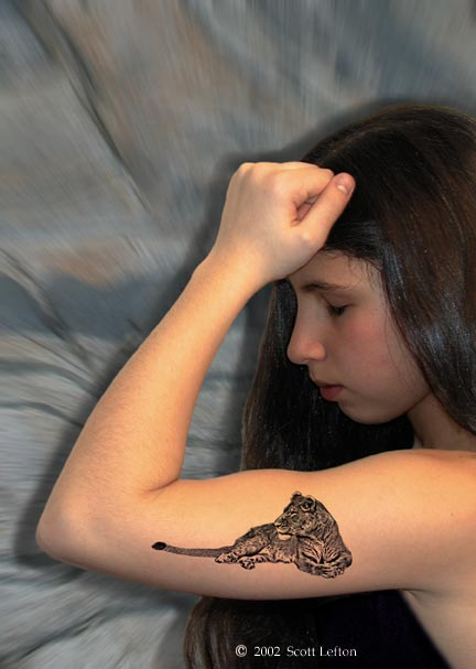 A young woman flexes her arm, with a tattoo of a lioness on her bicep.