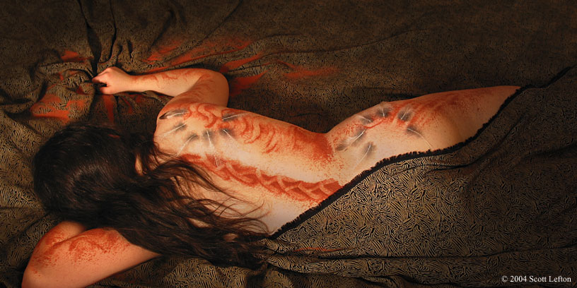 A woman lies in bed, clutching the sheets.  She's covered in feather designs and red sand painting.